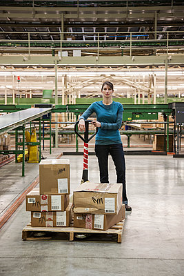 A Caucasian female warehouse worker in a distribution warehouse. - p1100m2002285 by Mint Images