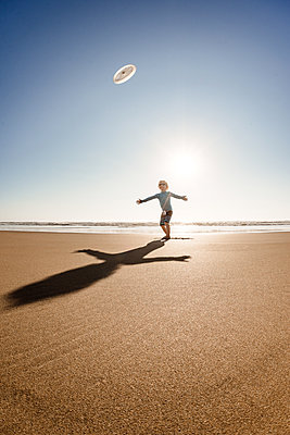 Young boy with arms outstretched playing at the beach on a summer day - p1166m2108135 by Cavan Images
