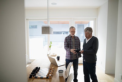 Senior male gay couple using digital camera near laptop in dining room - p1192m1517061 by Hero Images