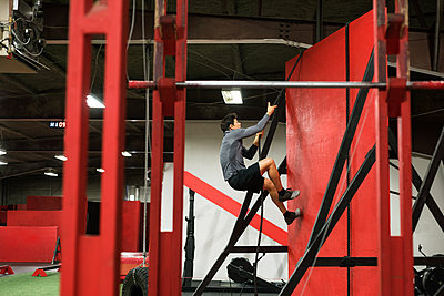 Muscular man climbing a wall with rope in the gym - p1315m1566490 by Wavebreak