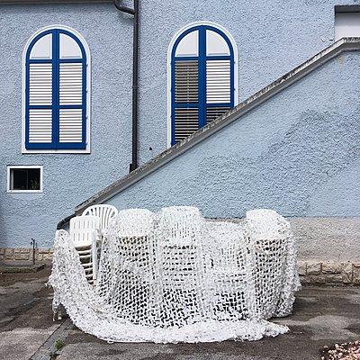 Gestapelte Stühle bedeckt mit einem Netz - p1401m2288272 von Jens Goldbeck