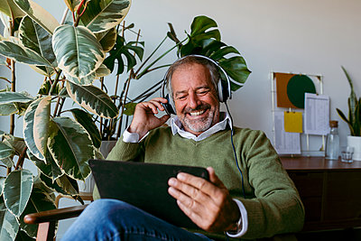 Smiling mature men wearing headphones while using digital tablet at home - p300m2226644 by Valentina Barreto