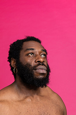 Black man looking at the side with a pink background - p590m2092890 by Philippe Dureuil