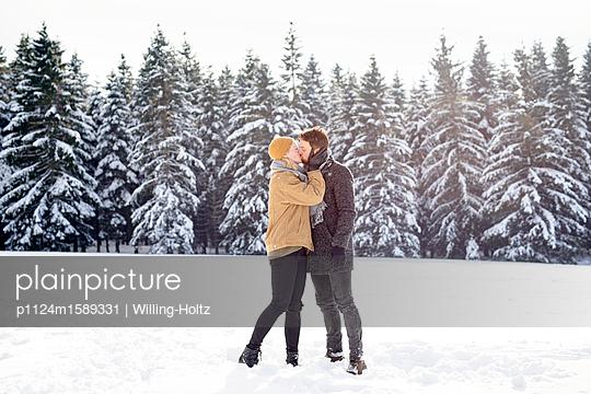 Junges Paar küsst sich in einer Schneelandschaft - p1124m1589331 von Willing-Holtz