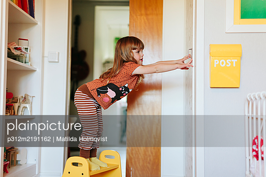 Girl opening door - p312m2191162 by Matilda Holmqvist