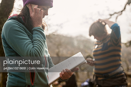 Mature woman using cell phone with notebook - p429m1021865f by Colin Hawkins