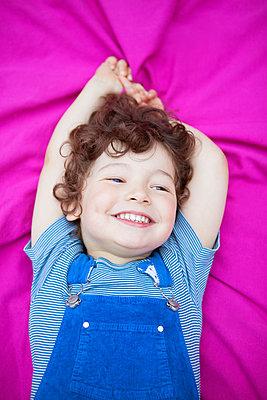 Junge liegt auf Decke und lacht - p045m1440055 von Jasmin Sander