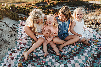 Four sisters sitting on blanket at beach laughing at sunset - p1166m2165883 by Cavan Images
