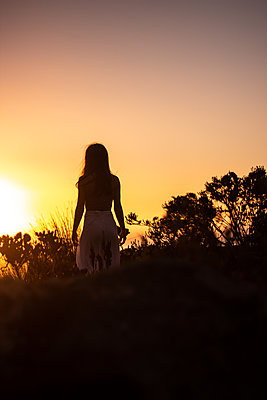 Silhouette of teenage girl at sunset - p1640m2245878 by Holly & John