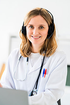 Smiling female medical professional wearing headphones during online consultation at medical clinic - p300m2265427 by Giorgio Fochesato