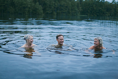 Happy friends enjoying in lake - p301m1406526 by Isabella Ståhl