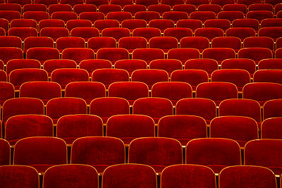 Rows of empty red chairs in a theater - p397m1573939 by Peter Glass