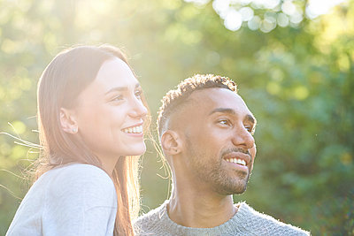 Close-up of smiling young couple looking away in public park - p623m2294778 by Eric Audras