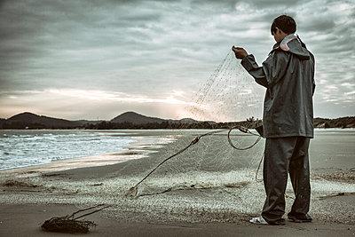 Fisherman tends to his net on Minh Chau Beach, Quan Lan Island, Quang Ninh Province, Vietnam, Southeast Asia - p934m1071228 by Francis Roux photography