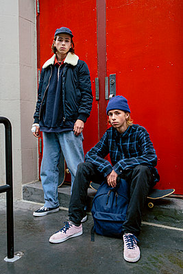 Portrait of confident male friends with skateboards against closed doors - p1166m2112546 by Cavan Images