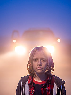 Portrait of tween with shoulder length hair backlit by headlights - p1166m2153411 by Cavan Images