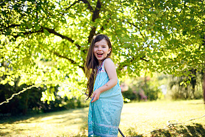 Cheerful girl with pipe in garden - p300m2273734 by Biederbick&Rumpf