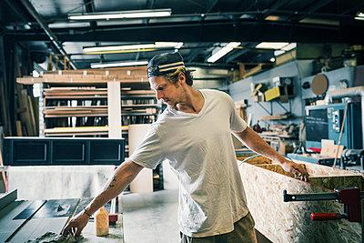 Carpenter making furniture at workshop - p426m1062630f by Maskot