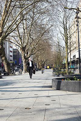 Mature businessman walking on sidewalk - p429m803575f by Liam Norris