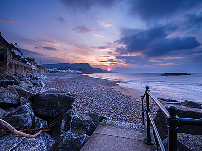 Sunrise looking along the beach at the picturesque seaside town of Sidmouth, Devon, England, United Kingdom - p871m2114118 by Baxter Bradford