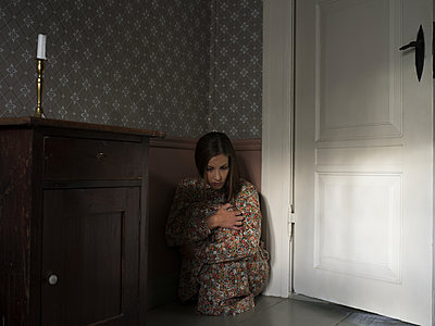 Woman squatting in a corner - p945m1154636 by aurelia frey