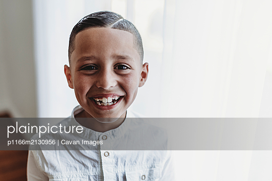 Portrait of young boy smiling at camera in natural light studio - p1166m2130956 by Cavan Images