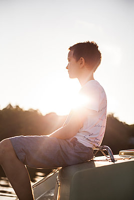Berlin boy sitting on boat on the lakefront - p1394m1440826 by benjamin tafel