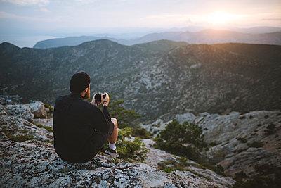 Italy, Liguria, La Spezia, Man looking at mountain range from mountain top - p1427m2213571 by Oleksii Karamanov