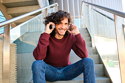 Smiling young man with headphones sitting on steps of office building - p300m2273613 by Antonio Ovejero Diaz