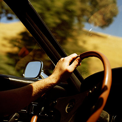 A person's hand on a steering wheel - p3011256f by fStop