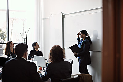 Businesswoman giving presentation to colleagues in office meeting - p426m2117087 by Maskot