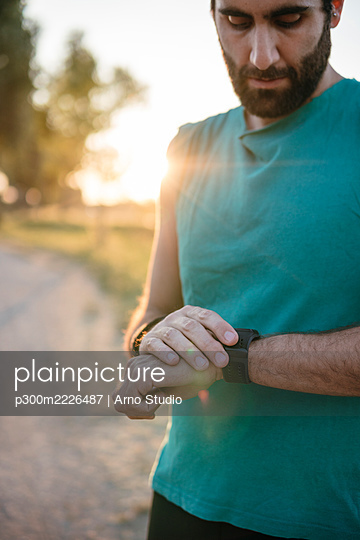 Young male athlete looking at smart watch while standing park - p300m2226487 by Arno Studio