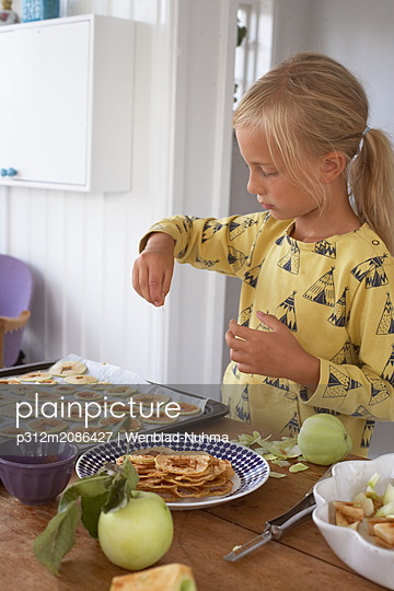 Girl preparing dried apples - p312m2086427 by Wenblad-Nuhma