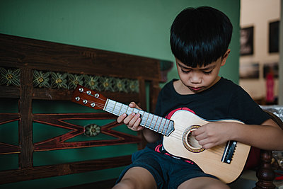 Asian boy playing guitar - p1166m2131255 by Cavan Images
