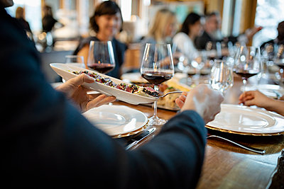 Close up man eating tapas and drinking wine at restaurant table - p1192m2047451 by Hero Images