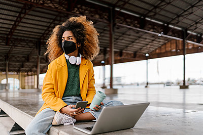 Valencia, Spain. Young woman with afro hair with face mask, seated using laptop computer. - p300m2265807 von Ezequiel Giménez