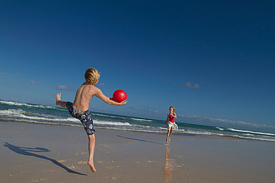Children playing with red ball on beach - p42914475f by jackSTAR