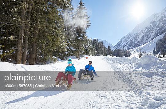 Couple sledding in snow-covered landscape - p300m1587085 von Christian Vorhofer