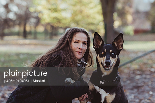Side view portrait of smiling woman with dog at park - p426m2194951 by Maskot