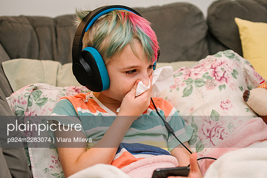 Canada, Ontario, Boy with colorful hair and headphones blowing nose on sofa - p924m2283074 by Viara Mileva