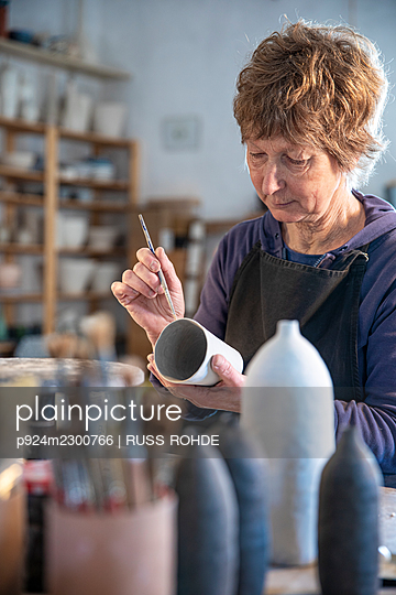 Spain, Baleares, Woman painting ceramics in workshop - p924m2300766 by RUSS ROHDE