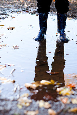 Anonymous child standing in a puddle - p1228m1511166 by Benjamin Harte