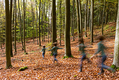 Children running through forest - p305m1586703 by Dirk Morla