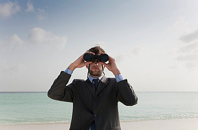 Businessman using binoculars on beach - p42914893 by Lost Horizon Images
