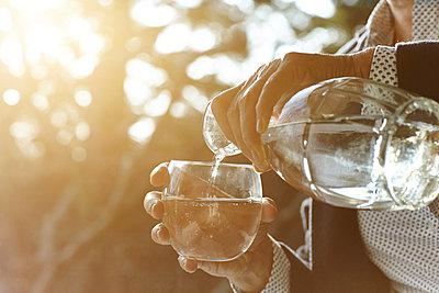 Hands of senior woman pouring glass of water by window - p429m1227374 by Maria Fuchs