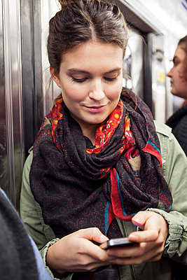 Young woman on subway using smartphone - p623m946681f by Sigrid Olsson