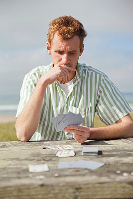 Man playing cards - p956m1044287 by Anna Quinn