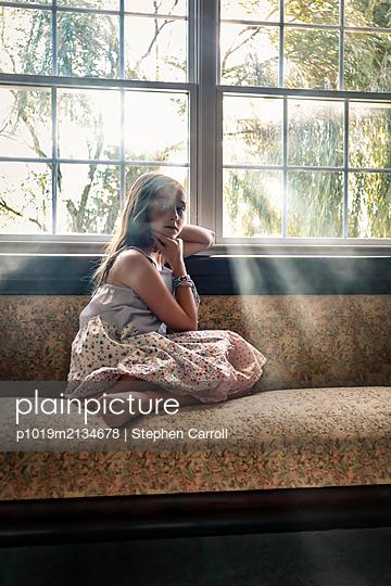 Junges Mädchen auf einem Sofa am Fenster - p1019m2134678 von Stephen Carroll