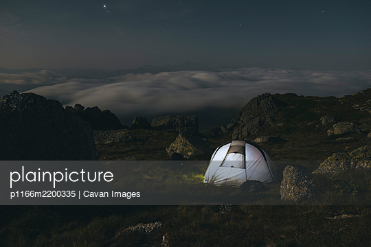 Mountain camping at night watching clouds unroll, Cantabria, Spain - p1166m2200335 by Cavan Images