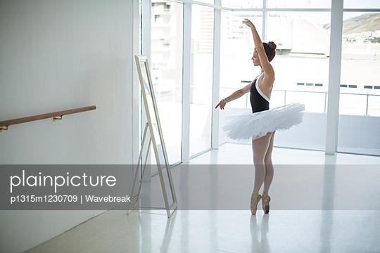 Ballerina practicing ballet dance in front of mirror - p1315m1230709 by Wavebreak